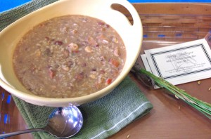 a delicious bowl of gumbo accented by sprigs of rice and a warm colored wooden tray