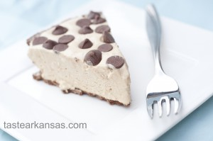 This photo shows a picture of no bake peanut butter pie. The pie is light and fluffy, on a chocolate cookie crust with milk chocolate chips dotting the top of the pie.
