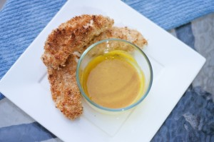A crisp white plate of golden oven baked chicken tenders and a sweet honey mustard.