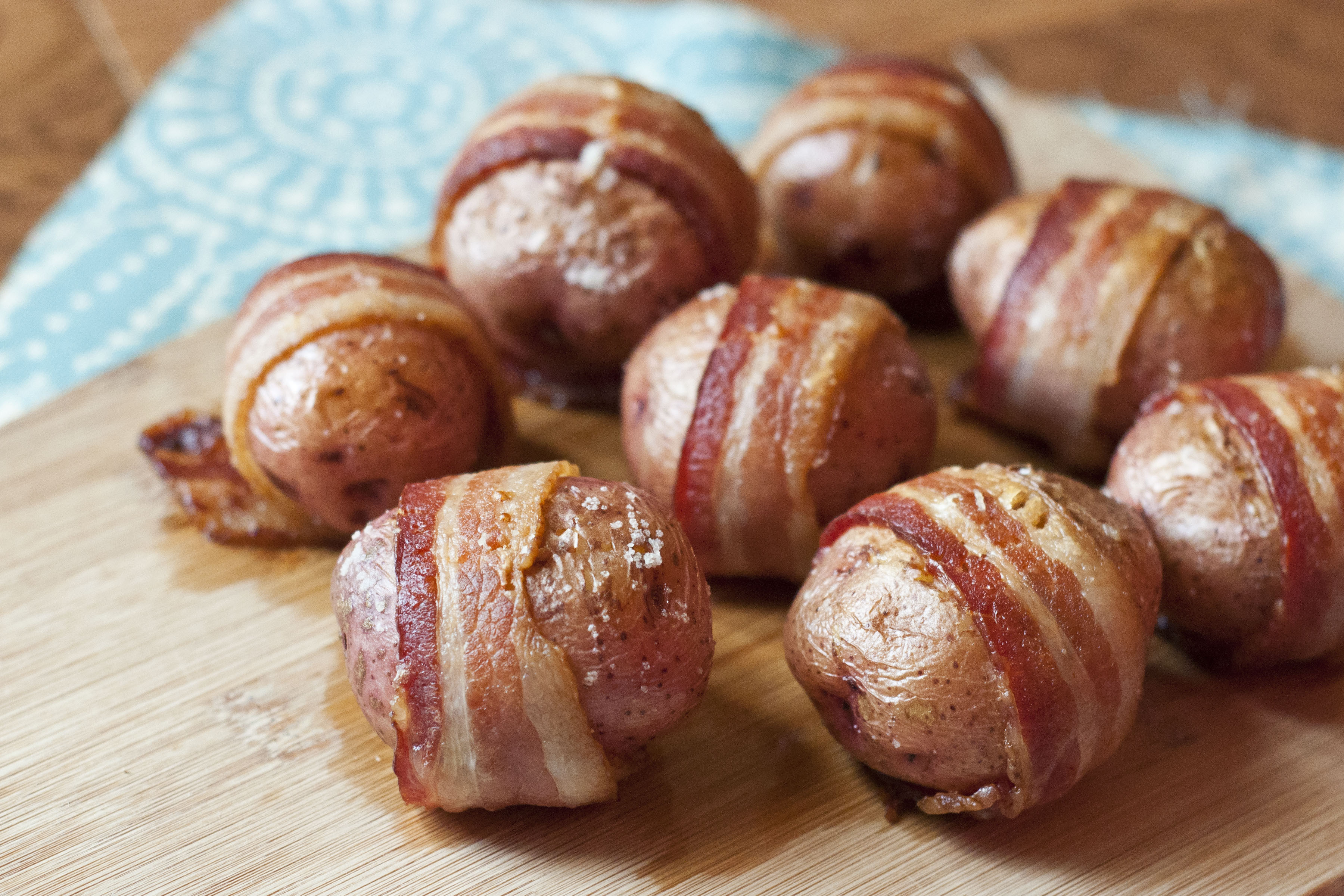 This image shows steamy tender red potatoes wrapped with crispy Petit Jean Bacon on a wooden cutting board, ready to eat.