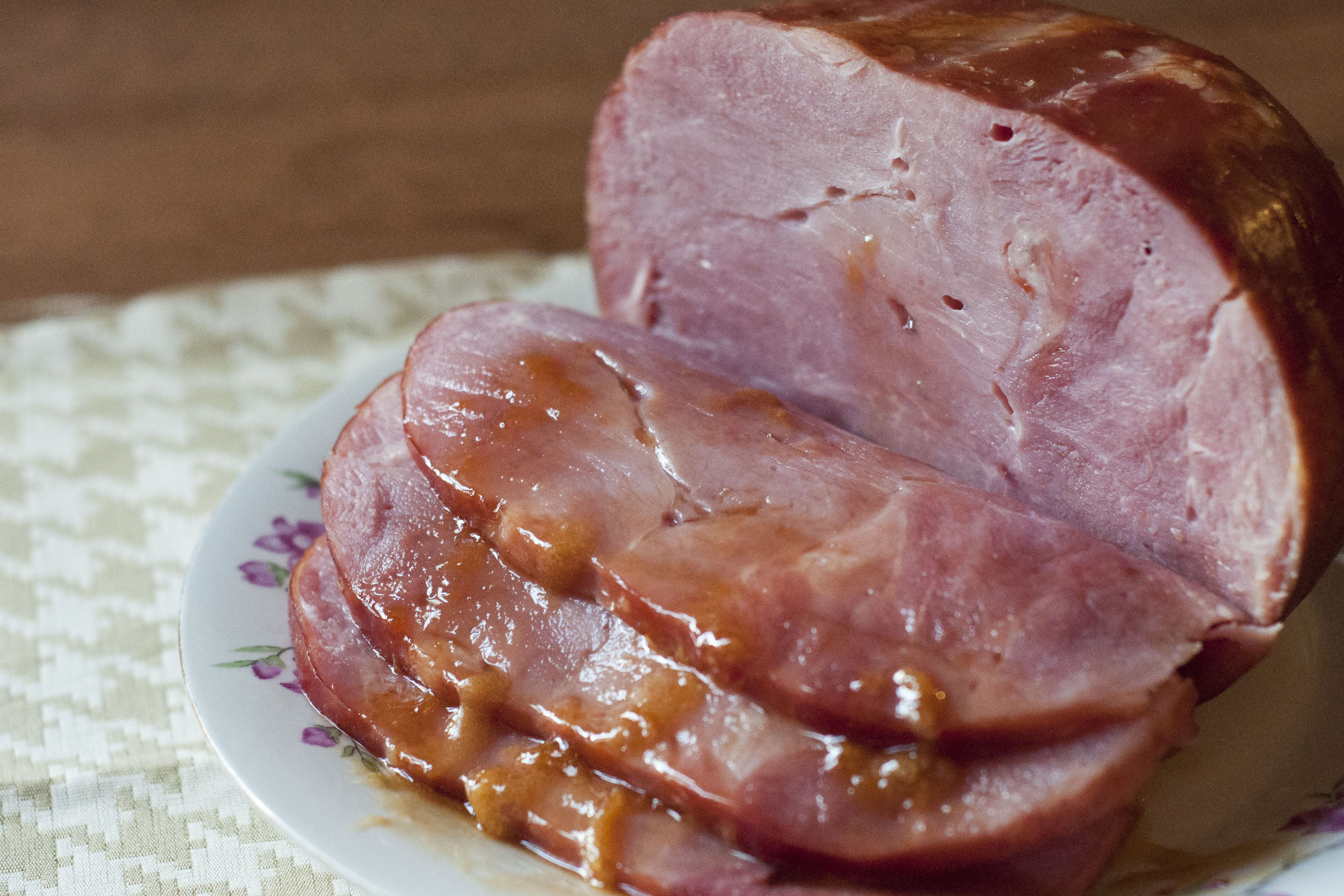 This photo shows a partially sliced ham from Petit Jean Meats with a drizzle of apricot glaze.