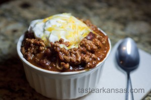 a steamy bowl of chili with a dollop of greek yogurt and shredded cheese