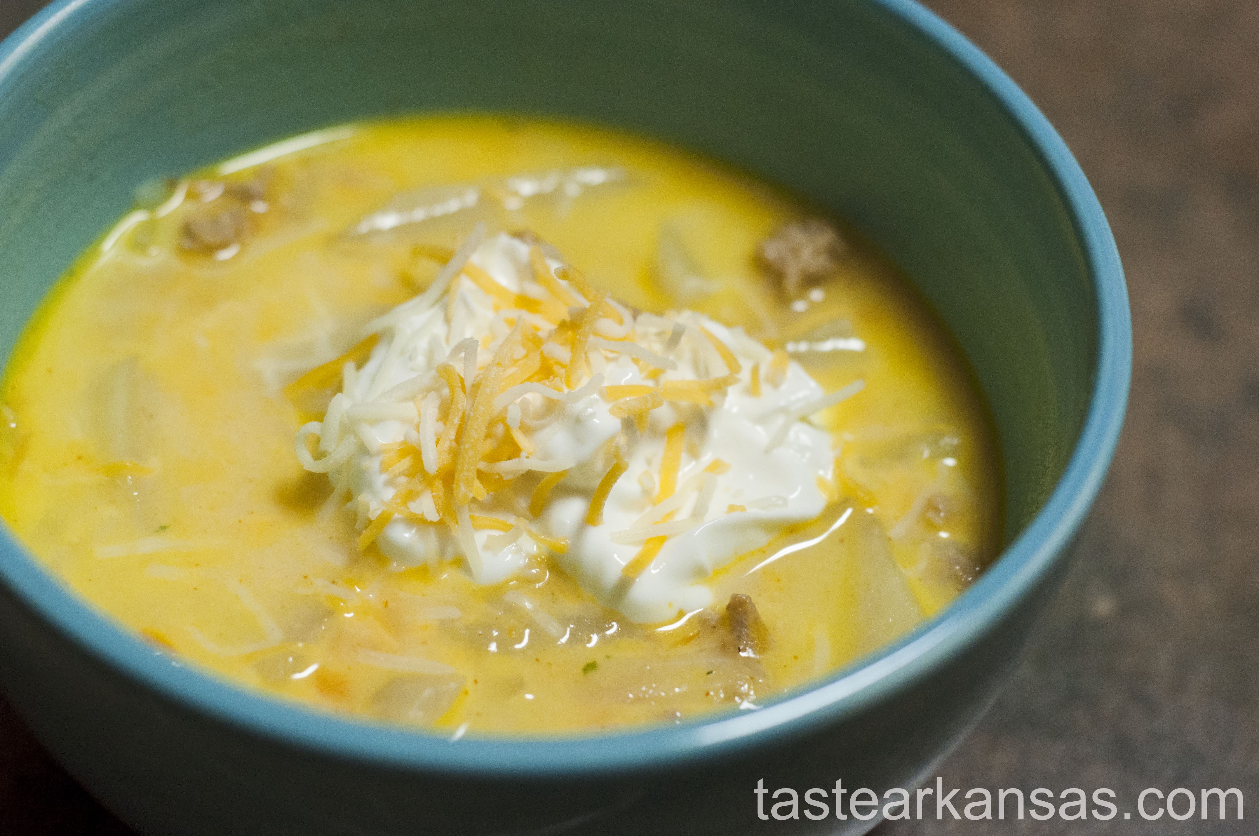 this picture is of a warm steamy bowl of turkey cheeseburger soup