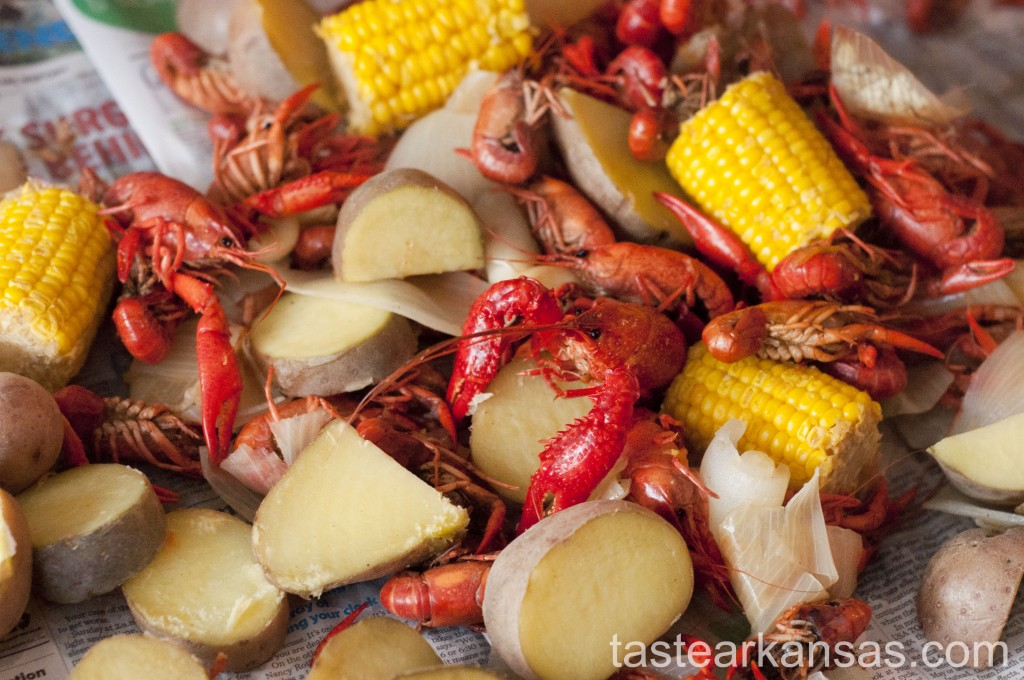 this image is of a crawfish boil, with crawfish, corn, onions, potatoes and garlic on a newspaper covered table