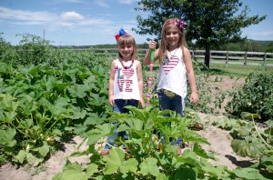 Josie and Abby working in the garden, one of their favorite activities on the farm.